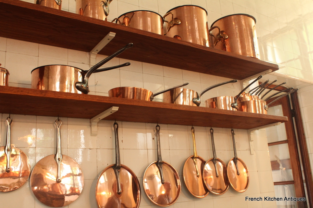 Several shelves hold a collection of copper stock pots, sauteuses and a wide variety of lids.